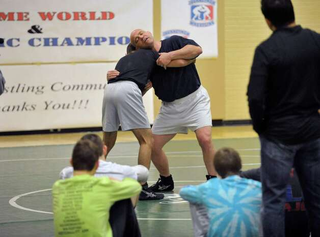 Olympic wrestler, Mark Schultz, right, shows wrestlers moves during a Journeymen Wrestling clinic at Colonie High School on Sunday, Dec. 14, 2014, in Colonie, N.Y.  (Paul Buckowski / Times Union) Photo: Paul Buckowski / 00029845A