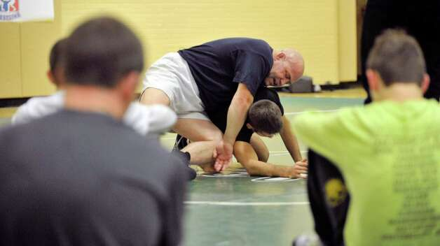 Olympic wrestler, Mark Schultz, top, demonstrates a wrestling move during a Journeymen Wrestling clinic at Colonie High School on Sunday, Dec. 14, 2014, in Colonie, N.Y.  (Paul Buckowski / Times Union) Photo: Paul Buckowski / 00029845A
