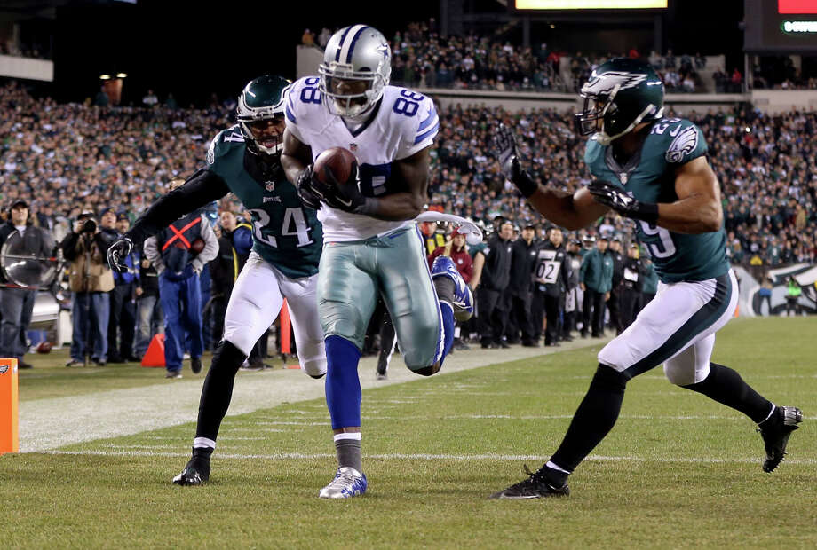 Dez Bryant of the Cowboys catches a touchdown pass, one of his career-high three on the night, against Bradley Fletcher (left) and Nate Allen of the Eagles. Photo: Mitchell Leff / Getty Images / 2014 Getty Images