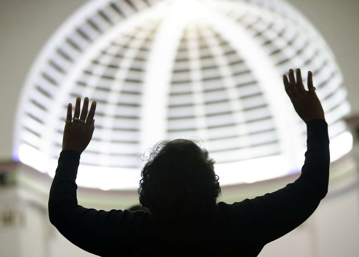 A parish member of Mt. Zion Church of God in Christ in Muskegon, Mich., worships at the beginning of the service on Sunday, Dec. 14, 2014. Many predominantly black churches across the country were to hold special services on the theme