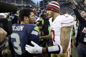 Seattle Seahawks quarterback Russell Wilson (3) and San Francisco 49ers quarterback Colin Kaepernick meet after an NFL football game, Sunday, Dec. 14, 2014, in Seattle. The Seahawks won 17-7. (AP Photo/Elaine Thompson)