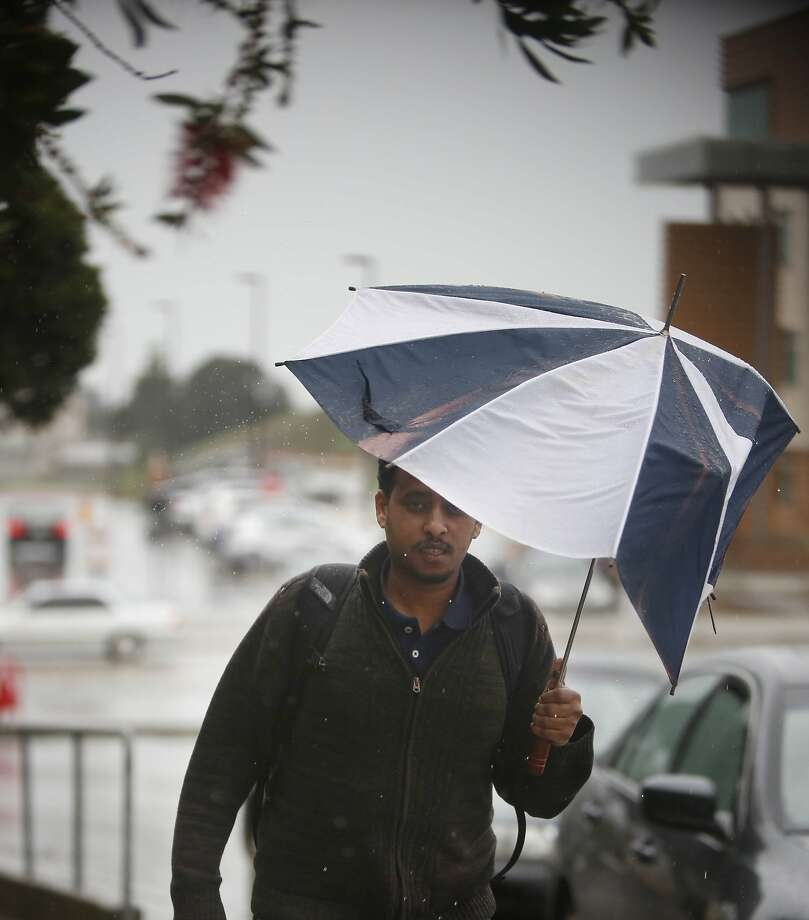 Bereket Haile, City College of San Francisco  student,  uses a broken umbrella to keep out of the rain on campus at City College of San Francisco  on  Monday, December 15, 2014 in San Francisco, Calif. Photo: Lea Suzuki, The Chronicle