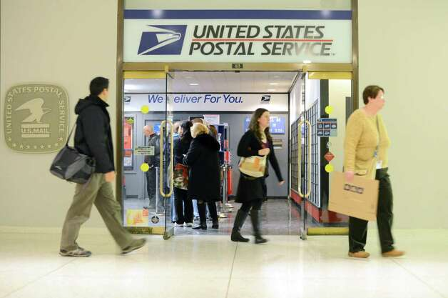 Customers lineup at the Empire State Plaza post office Monday afternoon, Dec. 15, 2014, on the concourse near Corning Tower in Albany, N.Y. The U.S. Postal Service predicted Monday would be the busiest day of the year for mailing cards, letters and packages. (Will Waldron/Times Union) Photo: WW
