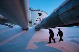 FILE PHOTO: Employees pass beneath pipes leading to oil storage tanks at the central processing plant for oil and gas at the Salym Petroleum Development oil fields near the Bazhenov shale formation in Salym, Russia, on Tuesday, Feb. 4, 2014. Oil extended losses below $60 a barrel amid speculation that OPEC's biggest members will defend market share against U.S. shale producers. Photographer: Andrey Rudakov/Bloomberg