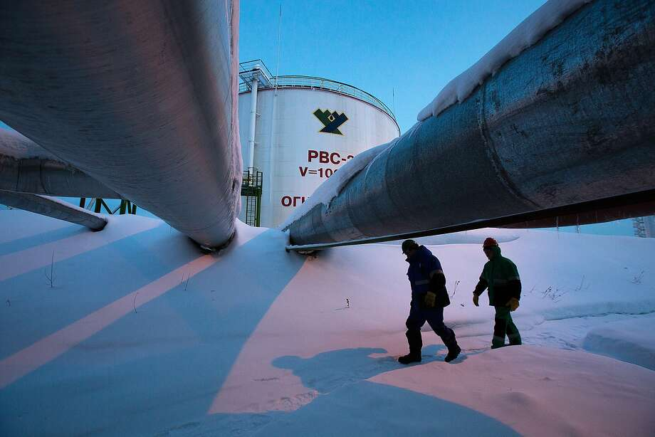 FILE PHOTO: Employees pass beneath pipes leading to oil storage tanks at the central processing plant for oil and gas at the Salym Petroleum Development oil fields near the Bazhenov shale formation in Salym, Russia, on Tuesday, Feb. 4, 2014. Oil extended losses below $60 a barrel amid speculation that OPEC's biggest members will defend market share against U.S. shale producers. Photographer: Andrey Rudakov/Bloomberg Photo: Andrey Rudakov, Bloomberg