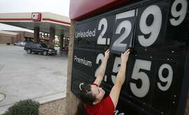 In this Friday, Dec. 12, 2014 photo, Quick Trip clerk Roxana Valverde adjusts the gas price sign numbers at a Tolleson, Ariz. QT convenience store as gas prices continue to tumble nationwide. The price of oil has fallen by nearly half in just six months, a surprising and steep plunge that has consumers cheering, producers howling and economists wringing their hands over whether this is a good or bad thing. (AP Photo/Ross D. Franklin)