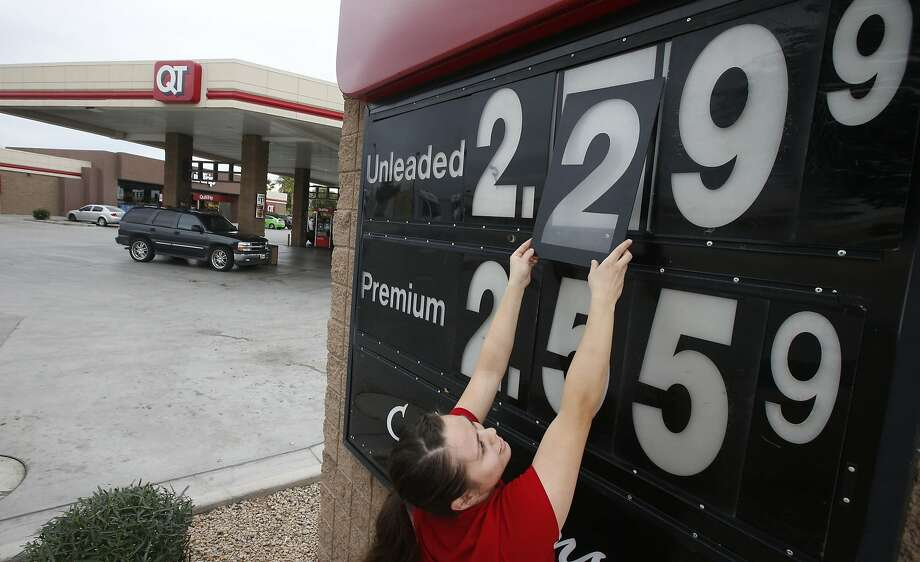 In this Friday, Dec. 12, 2014 photo, Quick Trip clerk Roxana Valverde adjusts the gas price sign numbers at a Tolleson, Ariz. QT convenience store as gas prices continue to tumble nationwide. The price of oil has fallen by nearly half in just six months, a surprising and steep plunge that has consumers cheering, producers howling and economists wringing their hands over whether this is a good or bad thing. Photo: Ross D. Franklin, Associated Press
