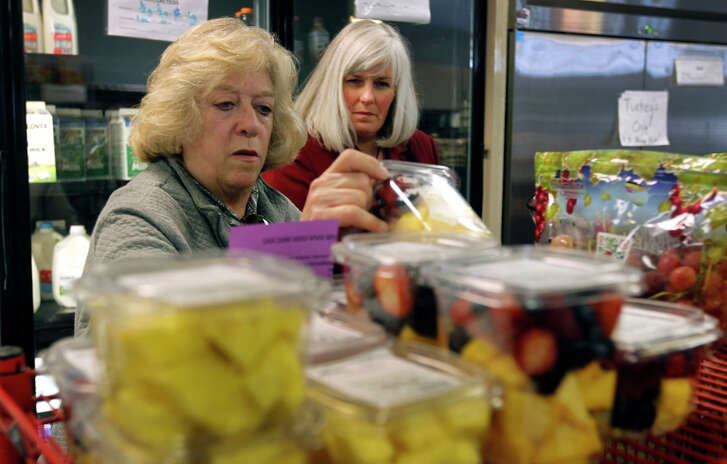 Sarah Meharg (left) selects groceries at a Napa food pantry, with help from food bank director Shirley King.