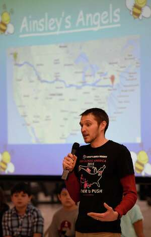 Shaun Evans, representing Ainsley's Angels, addresses the assembly and announces the gift of a Chariot to student Hunter Monday morning Dec. 15, 2014, at the Milton Terrace North Elementary School  in Ballston Spa, N.Y.   The first and third grades at Milton Terrace North El. raised the money to make the gift of a Chariot to Hunter.   (Skip Dickstein/Times Union) Photo: SKIP DICKSTEIN / 00029847A