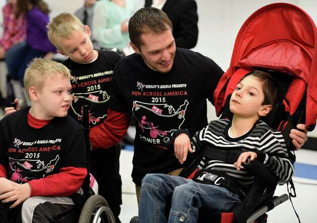 Shaun Evans, representing Ainsley's Angels, second from left, speaks to Hunter, left, who received a Chariot on Monday, Dec. 15, 2014, at the Milton Terrace North Elementary School  in Ballston Spa, N.Y.  With Evans are his two sons, Shamus, 9, and Simon, 7. The first and third grades at Milton Terrace North El. raised the money to make the gift of a Chariot to Hunter.   (Skip Dickstein/Times Union) Photo: SKIP DICKSTEIN / 00029847A