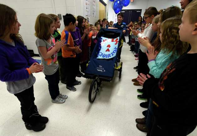 Members of the first and third grades, who raised the money, stand up and applaud for the gift of a Chariot  they presented to student Hunter on Monday morning Dec. 15, 2014 at the Milton Terrace North Elementary School  in Ballston Spa, N.Y.     (Skip Dickstein/Times Union) Photo: SKIP DICKSTEIN / 00029847A