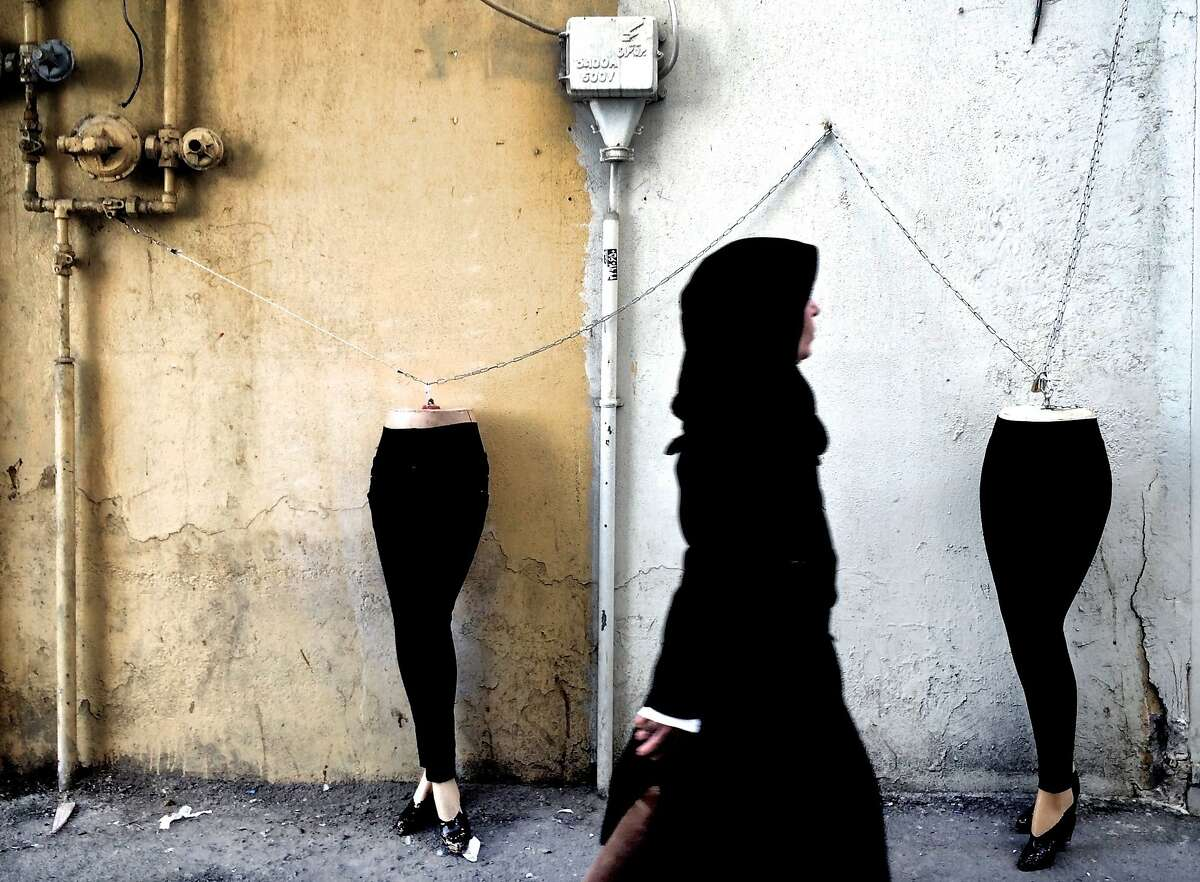 TOPSHOTS An Iranian woman walks past mannequins locked to a gas pipe in northern Tehran on December 15, 2014. AFP PHOTO/BEHROUZ MEHRIBEHROUZ MEHRI/AFP/Getty Images