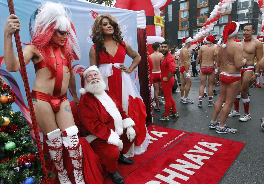 Santa Claus has his eyes on Suppository Spelling, who was posing for a post-race photo with Mercedez Munro (right) after the Santa Skivvies Run in San Francisco, Calif. on Saturday, Dec. 6, 2014. Participants in the 5th annual event organized by the San Francisco AIDS Foundation were encouraged to don holiday apparel or strip down to almost nothing and run 1.6 miles up Market Street from UN Plaza to Noe Street in the Castro. Photo: Paul Chinn, The Chronicle