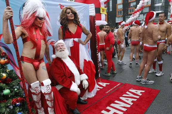 Santa Claus has his eyes on Suppository Spelling, who was posing for a post-race photo with Mercedez Munro (right) after the Santa Skivvies Run in San Francisco, Calif. on Saturday, Dec. 6, 2014. Participants in the 5th annual event organized by the San Francisco AIDS Foundation were encouraged to don holiday apparel or strip down to almost nothing and run 1.6 miles up Market Street from UN Plaza to Noe Street in the Castro.