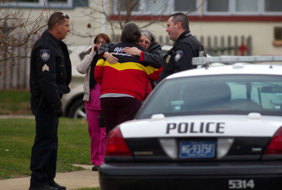 Residents in Lansdale, Pa., embrace while police investigate shootings that took place there and in neighboring communities that killed six people. The suspect's ex-wife was among the victims. Photo: Bill Fraser / Associated Press / Bucks County Courier Times