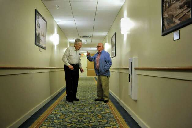 Neighbors, Hans Pohlsander, left, and Dick Pearce talk in the hallway between their two apartments on Monday, Dec. 15, 2014, in East Greenbush, N.Y.  Pearce fought for U.S. in WWII, Pohlsander fought for the Germans.   (Paul Buckowski / Times Union) Photo: Paul Buckowski / 00029849A