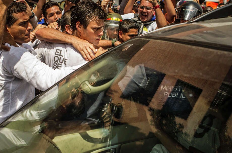 Opposition leader Leopoldo Lopez is taken into a car after surrendering to police in Caracas in February. Photo: MERIDITH KOHUT / New York Times / NYTNS