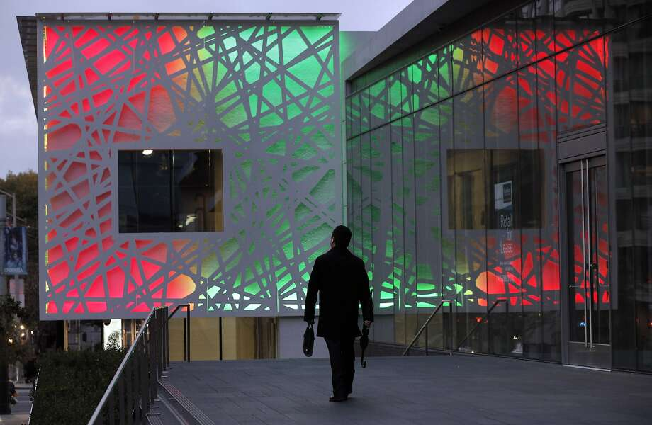 A man walks toward the new building at the northeast  corner of Third and Folsom Streets in San Francisco, Calif.,  on Wednesday, November 3, 2014. The building is quite a departure from the surrounding area as it was lighted for the first time. Photo: Carlos Avila Gonzalez, The Chronicle