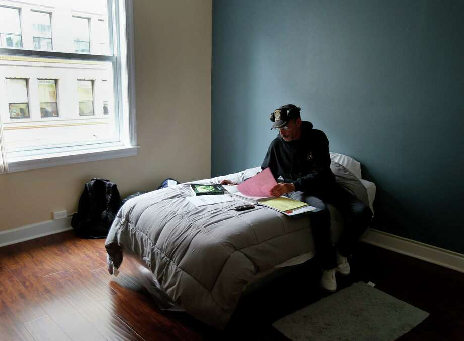 Joe Jackson looks over his economics homework in the room he now calls home. Photo: Brant Ward / The Chronicle / ONLINE_YES