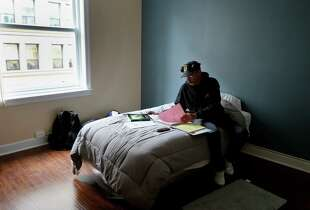 Joe Jackson looks over his economics homework in the room he now calls home Tuesday December 9, 2014. Joseph Jackson is a formerly homeless military veteran who has moved into the new supportive housing complex for veterans on Kearny Street in San Francisco, Calif. with the help of The Chronicle's Season of Sharing fund. Darrell Nunnally is also living there because of SOS.