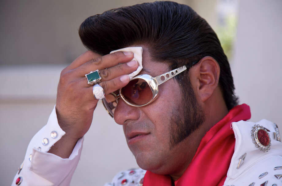"""Elvis impersonator Cristian Morales wipes sweat from his brow while standing out on The Strip posing for photos with tourists, Thursday, June 27, 2013 in Las Vegas. Morales preferred to stand out in the 112 degree heat of the day instead of working the cooler evening hours saying """"We'd much rather fight with the sun than fight with the drunk people."""" A high pressure system parking over the West is expected to bring temperatures this weekend and into next week that are extreme even for a region used to baking during the summer. (AP Photo/Julie Jacobson) Photo: Julie Jacobson / Associated Press / AP"""