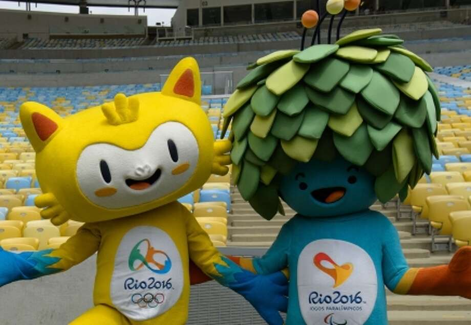 The mascots for the Rio 2016 Olympic Games (yellow) and the Rio 2016 Paralympic Games pose for photographers  at Maracana Stadium in Rio de Janeiro, Brazil, on December 4, 2014. The names of the mascots for Rio 2016 are open to the public to vote on their official website from three choices: Oba & Eba, Tiba Tuque & Esquindim, and Vinicius & Tom. The official names will be announced on December 14, 2014.  AFP PHOTO / YASUYOSHI CHIBAYASUYOSHI CHIBA/AFP/Getty Images Photo: YASUYOSHI CHIBA / AFP/Getty Images / AFP