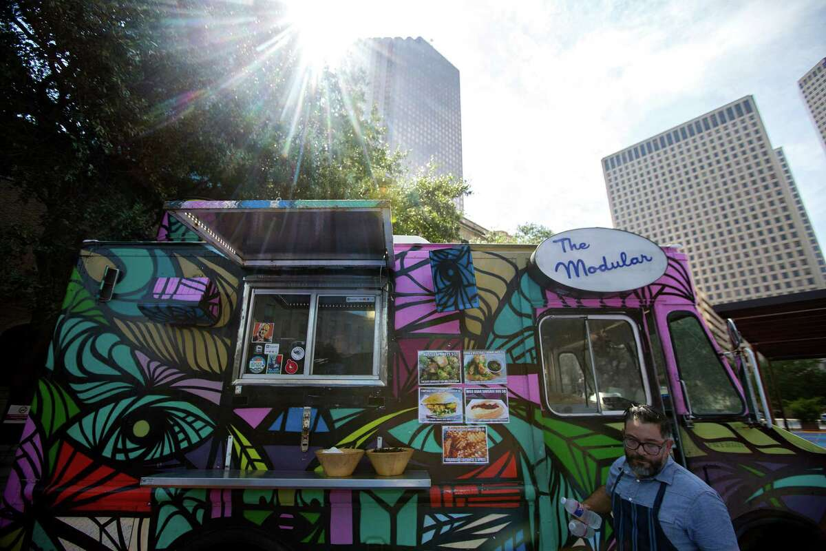 Outside Houston Public Library's Central Library downtown, Joshua Martinez, owner of The Modular food truck, closes the truck door before a press conference where Mayor Annise Parker announced that food trucks cooking with propane would be welcomed downtown and in the Texas Medical Center Friday, Sept. 26, 2014, in Houston. (Johnny Hanson / Houston Chronicle )