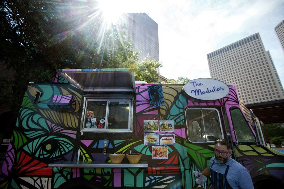 Outside Houston Public Library's Central Library downtown, Joshua Martinez, owner of The Modular food truck, closes the truck door before a press conference where Mayor Annise Parker announced that food trucks cooking with propane would be welcomed downtown and in the Texas Medical Center Friday, Sept. 26, 2014, in Houston. (Johnny Hanson / Houston Chronicle ) Photo: Johnny Hanson, Staff / © 2014  Houston Chronicle