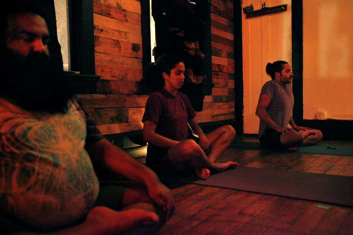 Praveen Sinha (left), Isamarie Perez and Nelson Sparks in the yoga class, which encourages students with a medicinal marijuana card to bring pot for personal consumption.