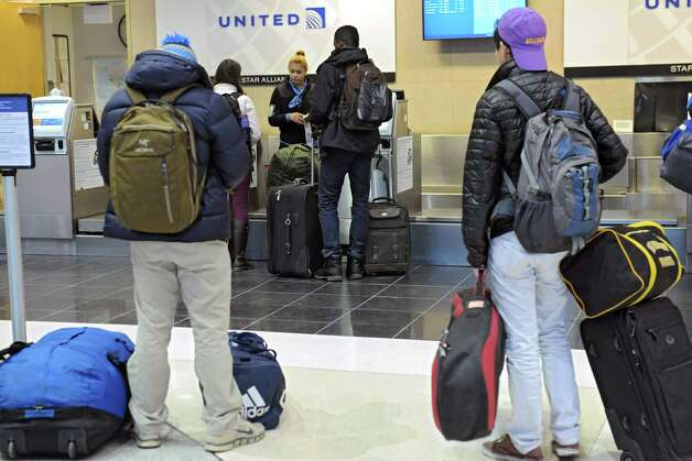 Passengers check in at Albany International Airport on Monday, Dec. 15, 2014 in Colonie, N.Y. Airfare still remains high despite oil price plunge. (Lori Van Buren / Times Union) Photo: Lori Van Buren / 00029861A