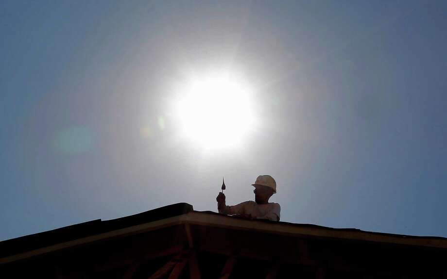 A roofer works under the midday sun in Gilbert, Ariz. A new study that matches 40 years of temperatures to economics found that days that averaged about 77 degrees ended up reducing people's income by about $5 a day, when compared to days that were about 20 degrees cooler. Photo: Associated Press File Photo / AP