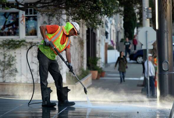 Peter Poliseri washes the sidewalk at 19th Street as construction crews finish the Castro Street improvement project between Market and 19th streets in San Francisco, Calif. on Wednesday, Oct. 29, 2014. Among the improvements are wider sidewalks and crosswalks painted in rainbow colors.