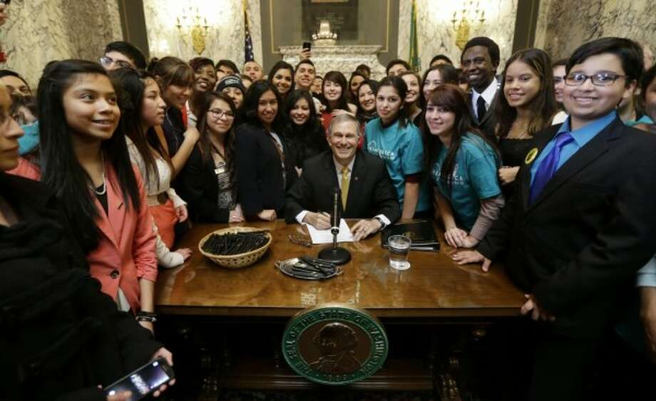 Washington Gov. Jay Inslee, flanked by students, signs the 2014 DREAM Act, expanding state financial aid to include undocumented students. State Senate Republicans buried the legislation, only to suddenly back it and pass it.  Will they do likewise with the Washington Voting Rights Act?  The House-passed measure is designed to bring district-based elections to towns, cities and counties with large Hispanic populations. (AP Photo/Ted S. Warren)