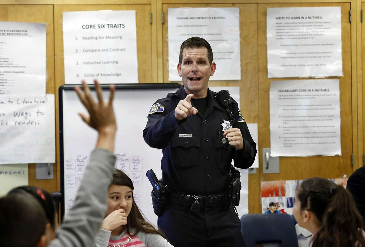 """FILE - In this Tuesday, Oct. 28, 2014 file photo, Officer Phil White of the San Jose Police Department teaches a """"Choices and Consequences"""" class for 5th grade students at Christopher Elementary School in San Jose, Calif. White is on leave as his department investigates comments posted online that threaten those protesting the recent deaths of unarmed black men in Ferguson, Missouri, and New York. In the tweets, White said he would kill anyone who threatens him or his family. He also said he would be off-duty at the movies with his gun if anyone """"feels they can't breathe or their lives matter."""" (AP Photo/Bay Area News Group, Gary Reyes)"""