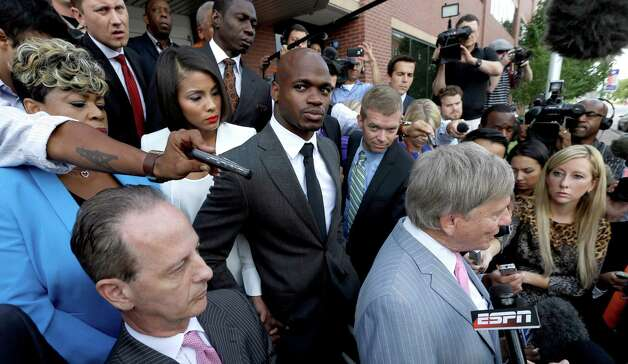 FILE - In this Oct. 8, 2014, file photo, Minnesota Vikings running back Adrian Peterson, center, stands with his wife Ashley Brown Peterson, center left, and mother Bonita Jackson, far left, as they listen to Peterson's attorney Rusty Hardin, right, outside the courthouse after making his first court appearance in Conroe, Texas. The NFL Players Association filed a federal lawsuit Monday, Dec. 15, 2014,  for Adrian Peterson, asking the court to dismiss an arbitration ruling that upheld the NFL's suspension of the star running back.  (AP Photo/David J. Phillip, Pool File) ORG XMIT: NY152 Photo: David J. Phillip / AP