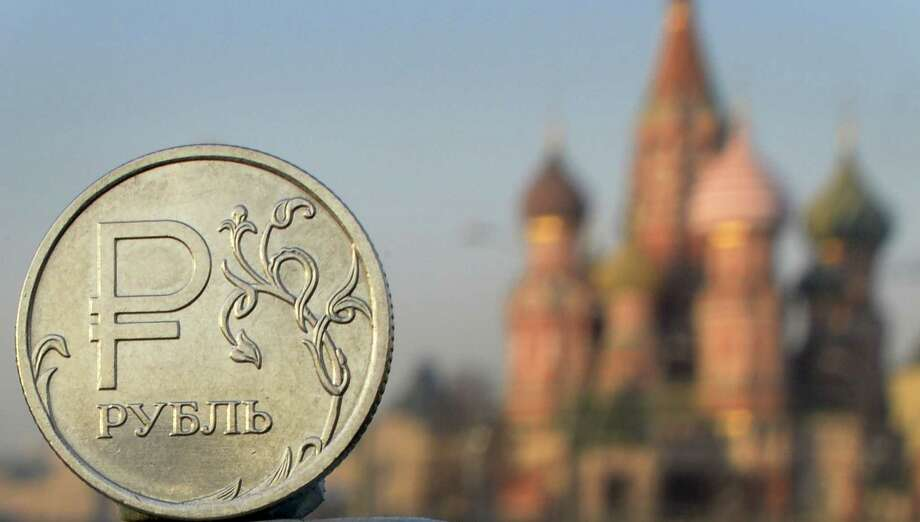 A Russian ruble is pictured in front of St. Basil's Cathedral. The ruble, hit by Western sanctions and oil prices, has lost nearly half its value this year. Photo: ALEXANDER NEMENOV, Staff / AFP