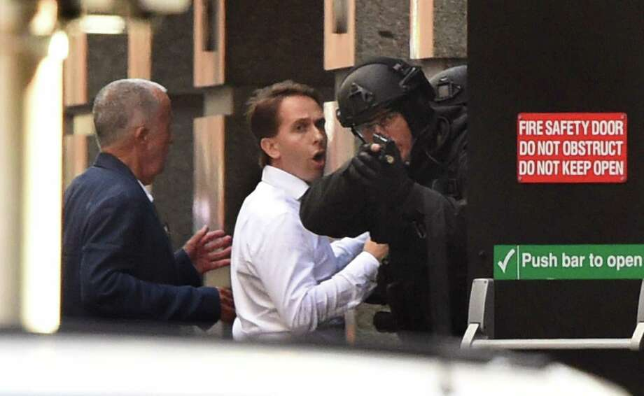 Two hostages run for cover behind a policeman  during Monday's hostage siege in the central business district of Sydney. A gunman held 17 people hostage inside a cafe for almost 16 hours before police rushed the building. Photo: WILLIAM WEST, Staff / AFP