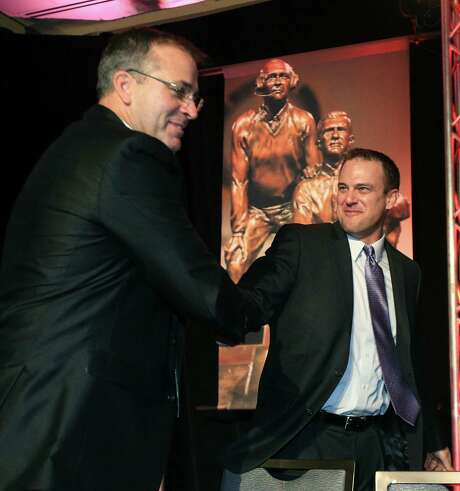 Tom Herman, right, of Ohio State, shakes hands with last year's winner Pat Narduzzi of Michigan State, after being announced as this year's  winner of the Broyles Award ceremony in Little Rock, Ark., Tuesday, Dec. 9, 2014. Herman was named the winner of the Broyles Award on Tuesday, after the Buckeyes made the College Football Playoff despite losing two starting quarterbacks to season-ending injuries.   (AP Photo/The Arkansas Democrat-Gazette, Staton Breidenthal)  ARKANSAS TIMES OUT; ARKANSAS BUSINESS OUT Photo: Staton Breidenthal, MBR / The Arkansas Democrat-Gazette