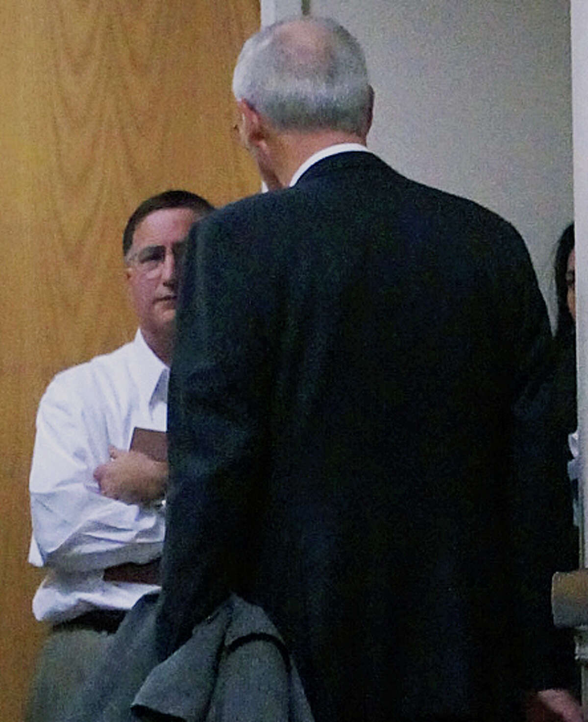 Supt. of Schools David Title, facing camera, huddles in the hallway with attorney Donald Houston after the Representative Town Meeting rejected a proposed contract with 38 school administrators.