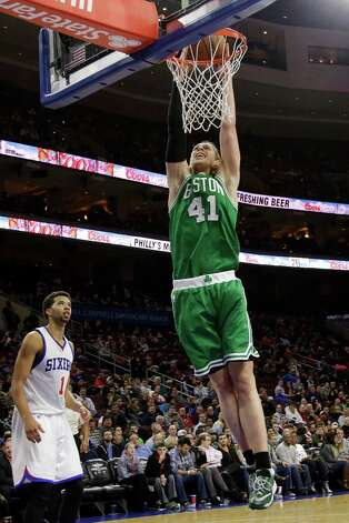 Boston Celtics' Kelly Olynyk (41) goes up for a dunk as Philadelphia 76ers' Michael Carter-Williams (1) looks on during the second half of an NBA basketball game, Monday, Dec. 15, 2014, in Philadelphia. Boston won 105-87. (AP Photo/Matt Slocum) ORG XMIT: PXC112 Photo: Matt Slocum / AP