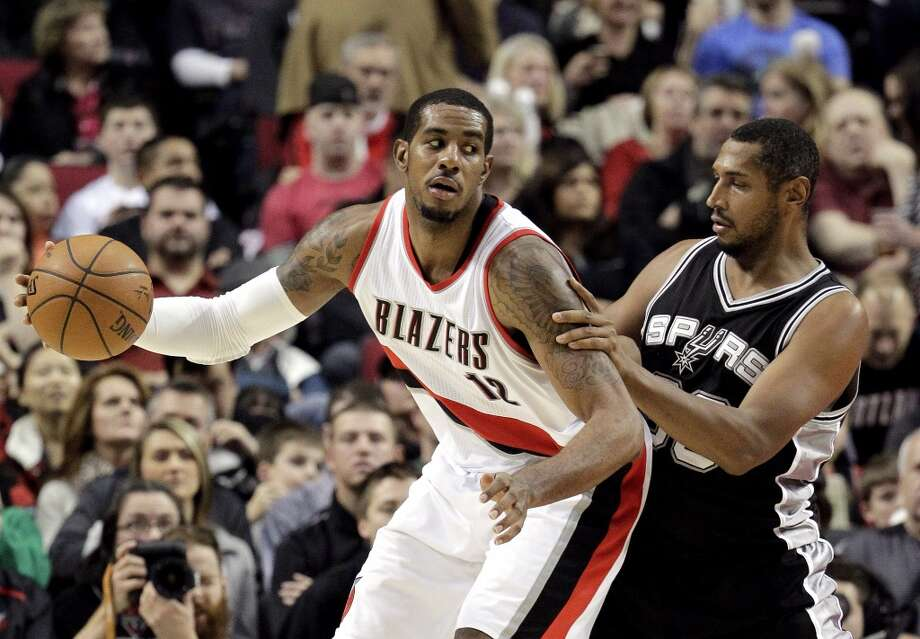 Portland Trail Blazers forward LaMarcus Aldridge, left, backs in on San Antonio Spurs center Boris Diaw, from France, during the second half of an NBA basketball game in Portland, Ore., Monday, Dec. 15, 2014.  Aldridge scored 23 points  and pulled in 14 rebounds as they beat the Spurs 108-95.(AP Photo/Don Ryan) Photo: Associated Press