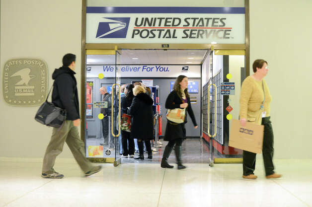 Customers lineup at the Empire State Plaza post office Monday afternoon, Dec. 15, 2014, on the concourse near Corning Tower in Albany, N.Y. The U.S. Postal Service predicted Monday would be the busiest day of the year for mailing cards, letters and packages. (Will Waldron/Times Union) Photo: WW, Albany Times Union