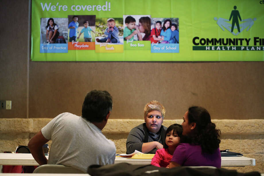 In-person assister Anel Treviño (center) helps a family  sign up for health insurance during an enrollment event in December 2014 at Progreso Hall on San Antonio's West Side. Photo: Express-News File Photo / © 2014 San Antonio Express-News