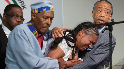 Esaw Garner, center, wife of Eric Garner, breaks down in the arms of Rev. Herbert Daughtry and Rev. Al Sharpton, right, during