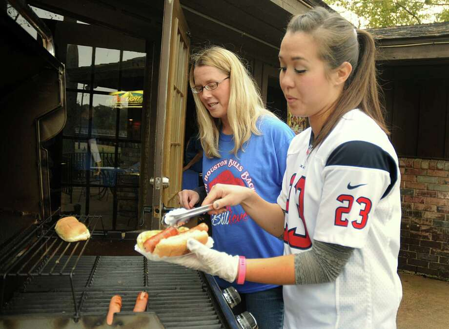 Buffalo Bills fan JuliAnna Butryn watches as Racks co-owner Jennifer Jones fixes Butryn a hot dog during the North Houston Bill Backers, a group of Buffalo Bills fans, watch party at Racks Bar and Grill, 17100 Kuykendahl in Spring. Racks owner Raymond Jones flew Buffalo's favorite hot dogs and mustard in for the game. Photograph by David Hopper Photo: David Hopper, Freelance / freelance