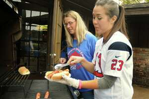 Buffalo Bills fan JuliAnna Butryn watches as Racks co-owner Jennifer Jones fixes Butryn a hot dog during the North Houston Bill Backers, a group of Buffalo Bills fans, watch party at Racks Bar and Grill, 17100 Kuykendahl in Spring. Racks owner Raymond Jones flew Buffalo's favorite hot dogs and mustard in for the game. Photograph by David Hopper