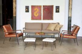The Alcott sofa and chair and the Edwin coffee table and ottoman are part of Cisco Home's Mid Century line; Morse sconces are also shown.