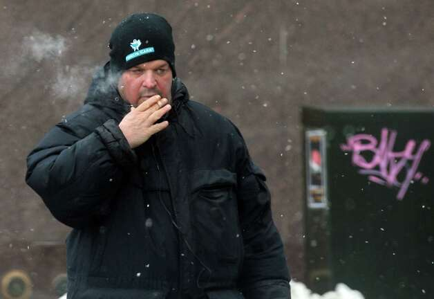 A man smokes a cigarette as he crosses State Street on Friday Dec. 12, 2014 in Troy , N.Y.  (Michael P. Farrell/Times Union) Photo: Michael P. Farrell / 00029812A