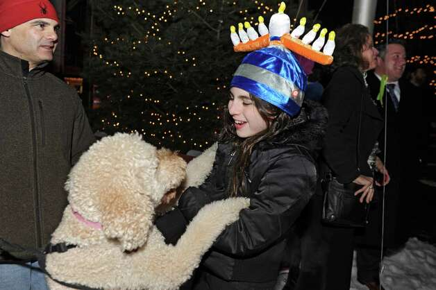 Ella Kasper, 12, of Delmar wears a menorah hat as she plays with her golden doodle dog named Doodle at a lighting of the menorah for Bethlehem Chabad's third annual Hanukkah celebration in the Four Corners on Tuesday, Dec. 16, 2014 in Delmar, N.Y. Ella's dad Rob Kasper stands at left.  (Lori Van Buren / Times Union) Photo: Lori Van Buren / 00029733A