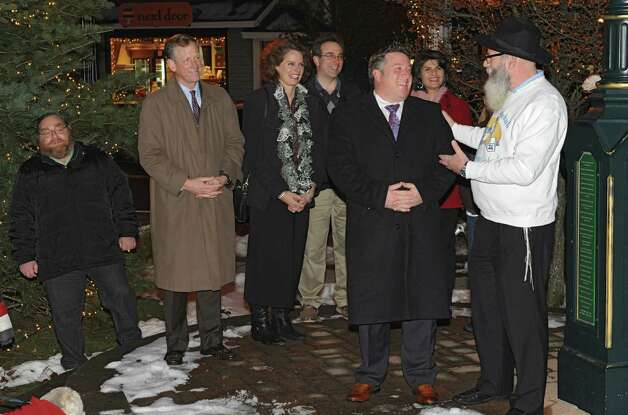 Rabbi Nachman Simon, right, jokes around with Albany County Executive Dan McCoy before lighting the menorah for Bethlehem Chabad's third annual Hanukkah celebration in the Four Corners on Tuesday, Dec. 16, 2014 in Delmar, N.Y. Other officials present were Bethlehem Town Supervisor John Clarkson, second from left, and state assembly member Patricia Fahy, center. (Lori Van Buren / Times Union) Photo: Lori Van Buren / 00029733A